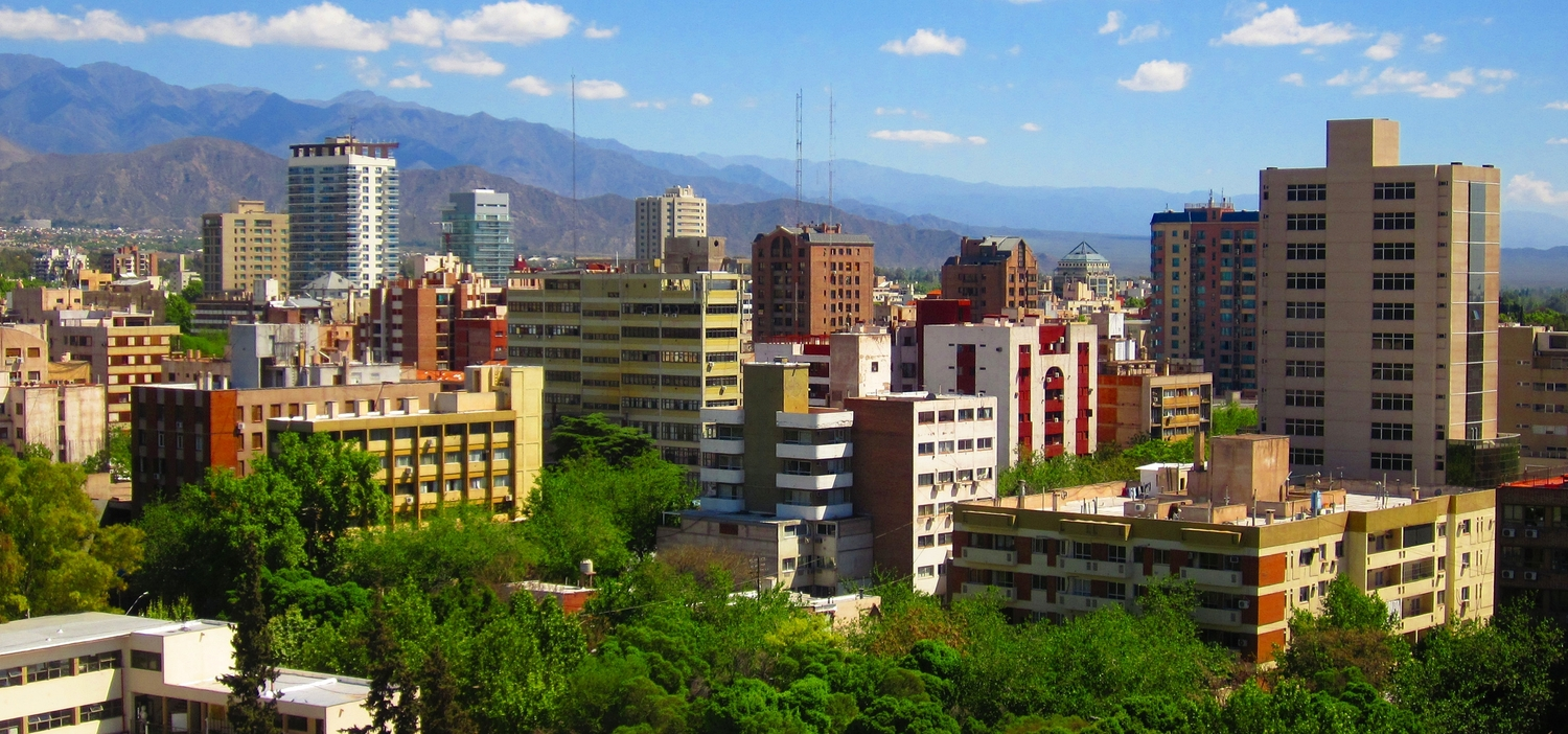 A typical view of mendoza city full of trees and big mountains.
